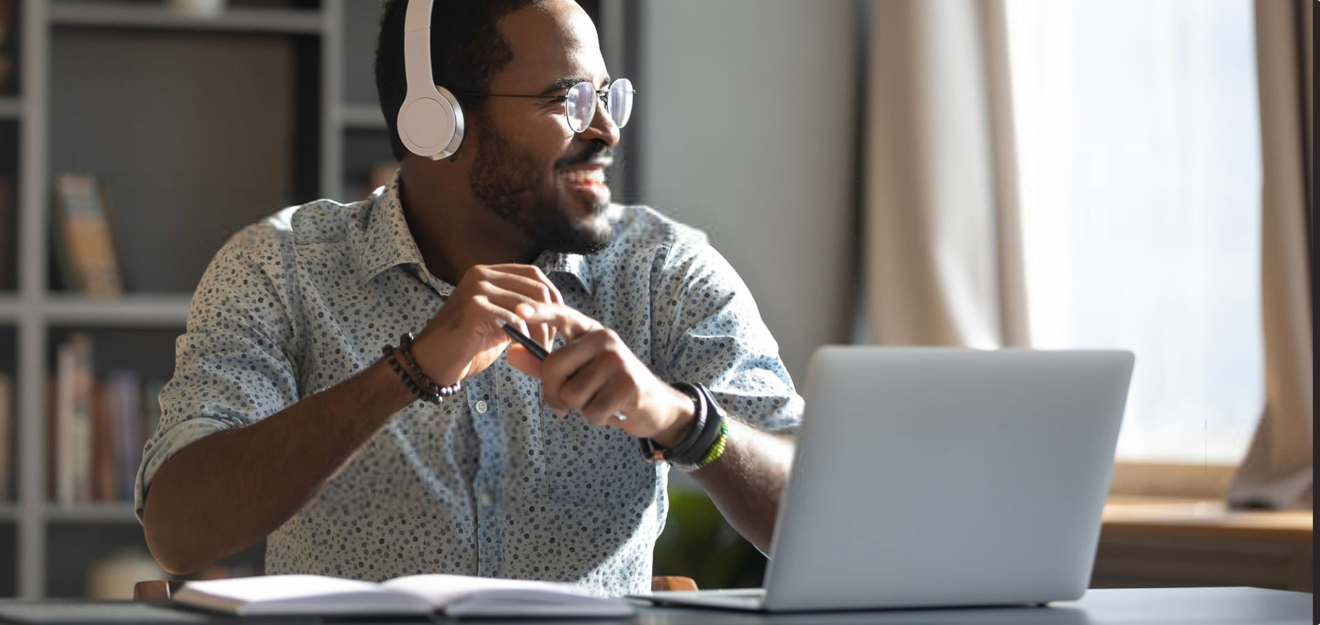 Young man with headphones looks off in the distance with a smile, sitting in front of a computer.